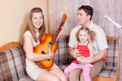 a family, the mother playing guitar