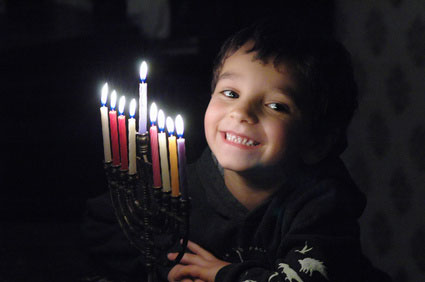 a kid lighting a chanukiyah