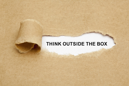 a tear in a paper reveals the words 'think outside the box'