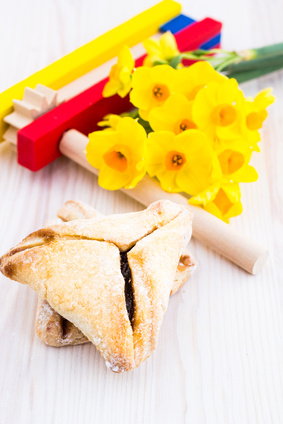 a table with hamentashen, noisemakers and flowers