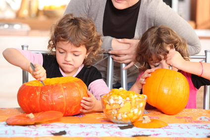 two kids carving pumpkins
