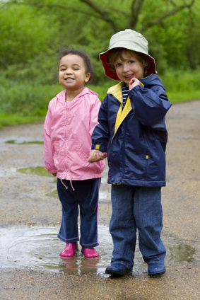 two smiling kids standing in a puddle