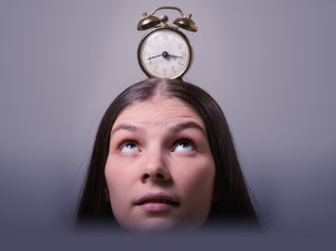 a girl with an alarm clock over her head